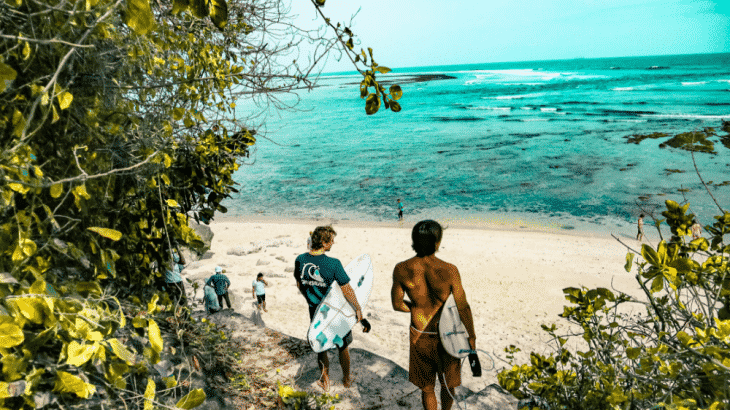 guys-holding-surf-boards-walking-to-turquoise-water