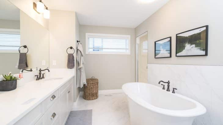 white-bathroom-tub-bathrobe-handing-on-door