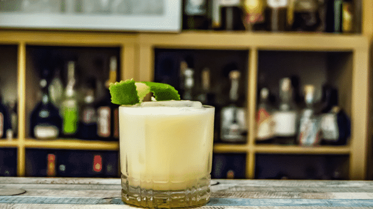 yellow-cocktail-with-lime-sitting-on-bar