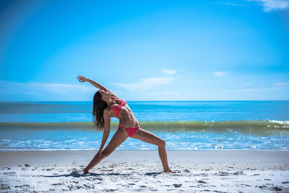 woman-doing-yoga-the-beach
