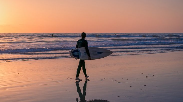 surfer-walking-with-board-sunset