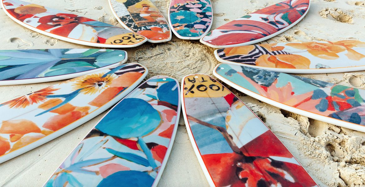 colorful surfboards in a circle laying flat on the beach
