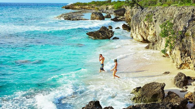 beach-snorkelers-turquoise-ocean-cliffs