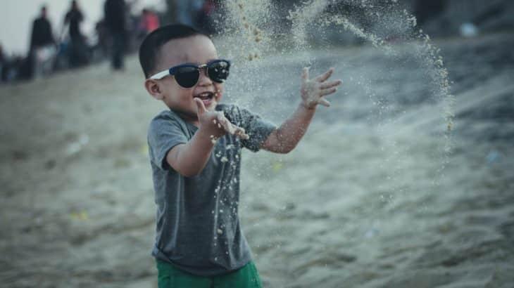 child-playing-sand-beach