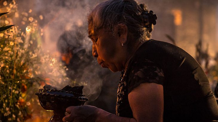 older-woman-blowing-on-copal-incense-day-of-the-dead-mexico