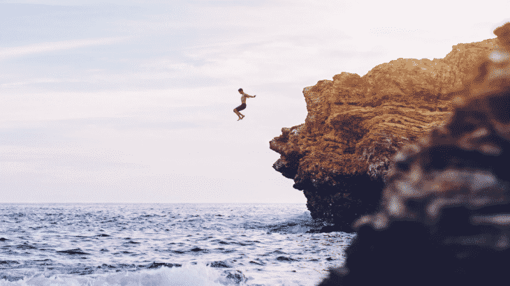 man-jumping-into-ocean-off-cliff
