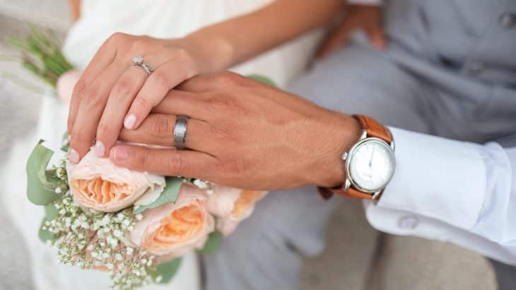 couples-hands-on-bouquet-wedding-rings-watch