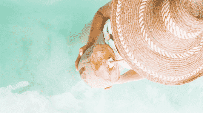 woman-holding-coconut-view-from-top-her-hat