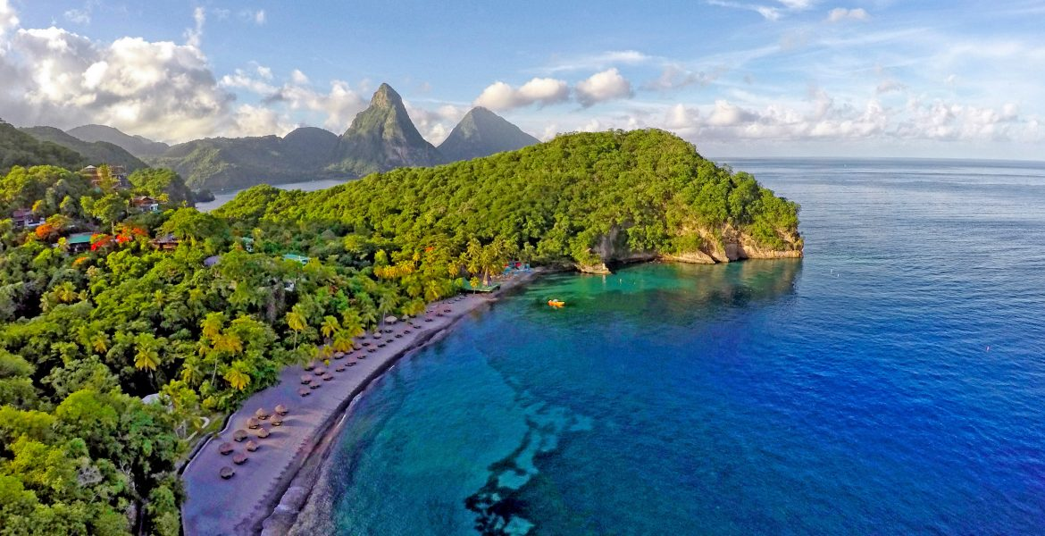 cresent-shaped-cove-from-above-blue-water-green-jungle