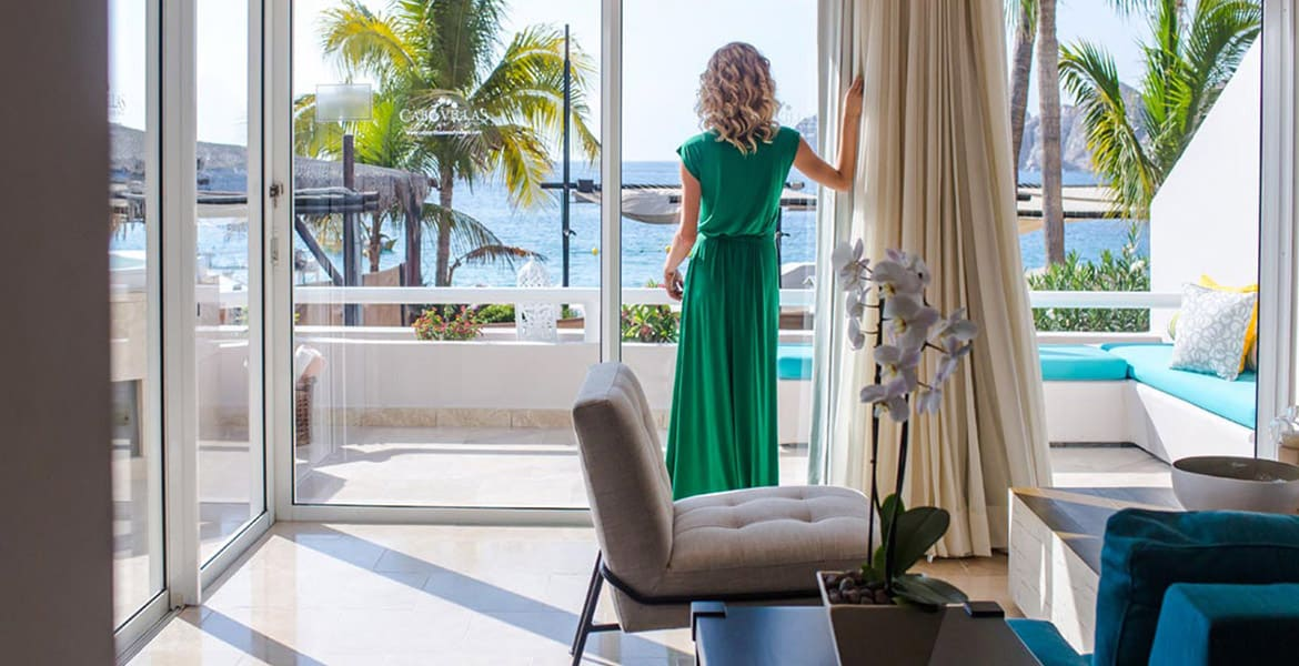 woman-in-long-green-dress-looking-out-open-wall-at-ocean