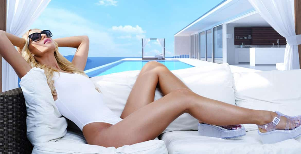 woman-white-bathing-suit-laying-on-white-couch-in-front-of-pool