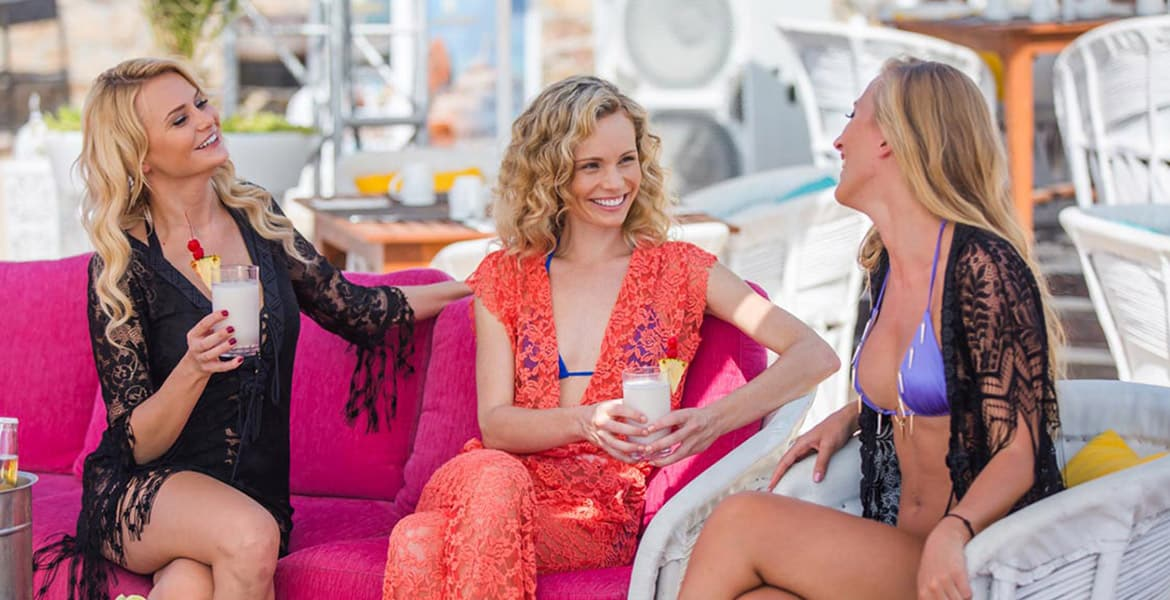 three-women-sitting-pink-couch-holding-cocktails