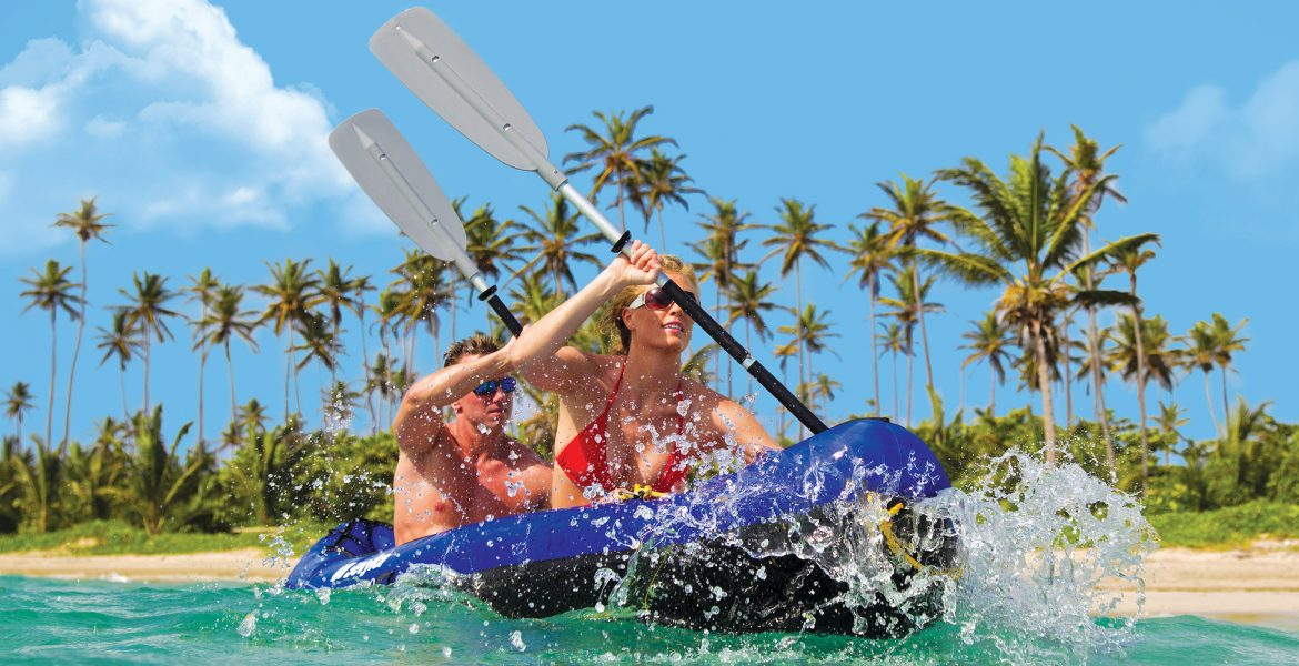 couple-kayaking-clear-water-green-palm-trees