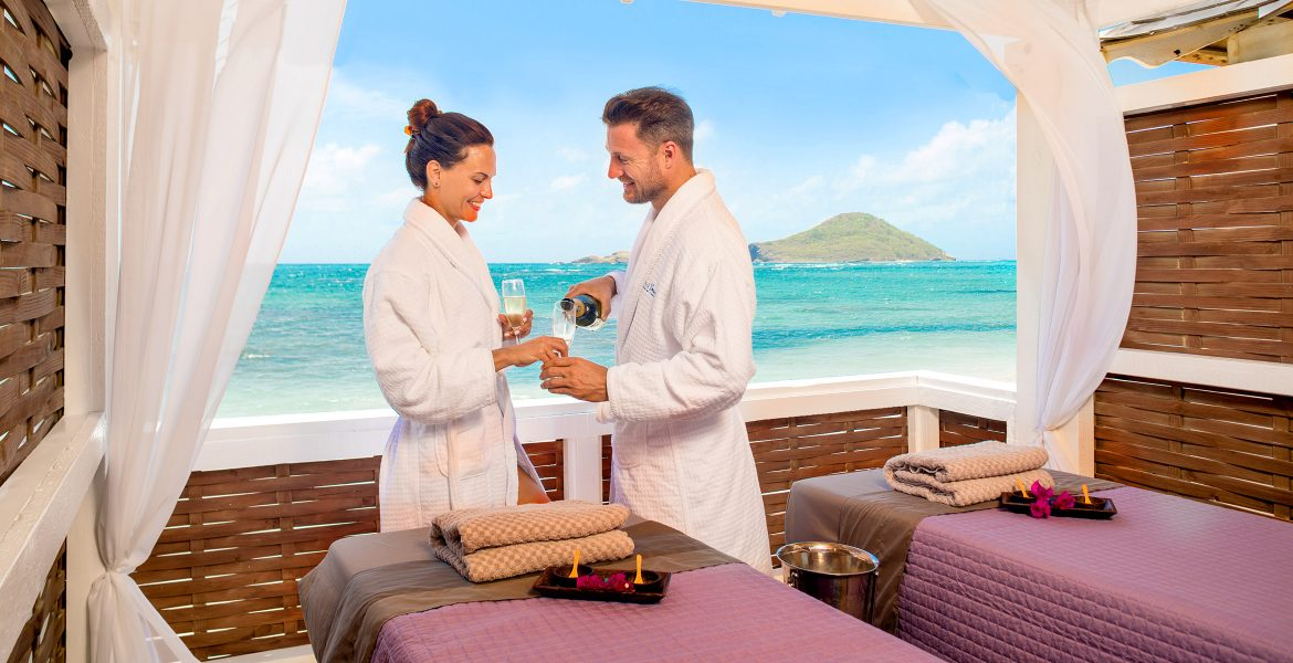 couple-at-open-spa-room-overlooking-blue-sea-green-island