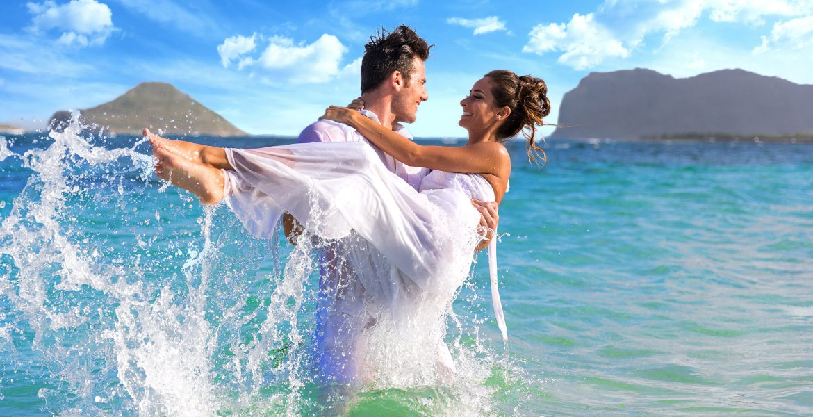 groom-holding-bride-in-clear-ocean-wearing-white
