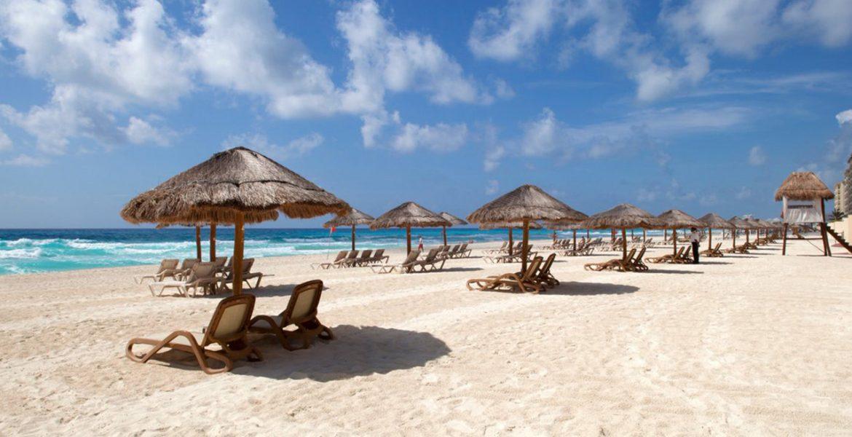 white-sand-beach-tiki-style-umbrellas-over-loungers