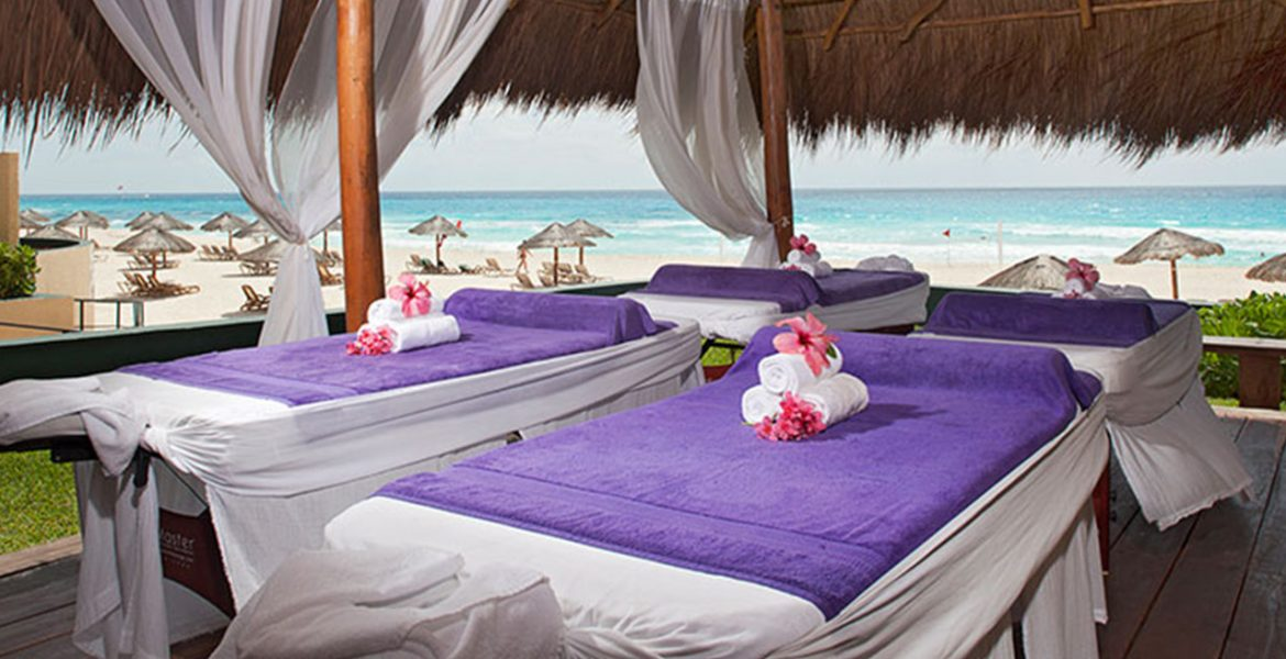 massage-tables-with-purple-blankets-on-beach