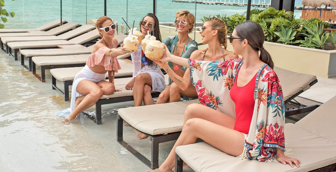 women-enjoying-coconut-drinks-by-beach