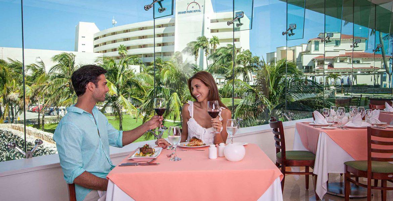 couple-enjoying-wine-outside-green-garden-behind
