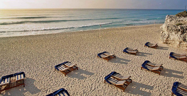 beach-loungers-white-sand-ocean-sunset