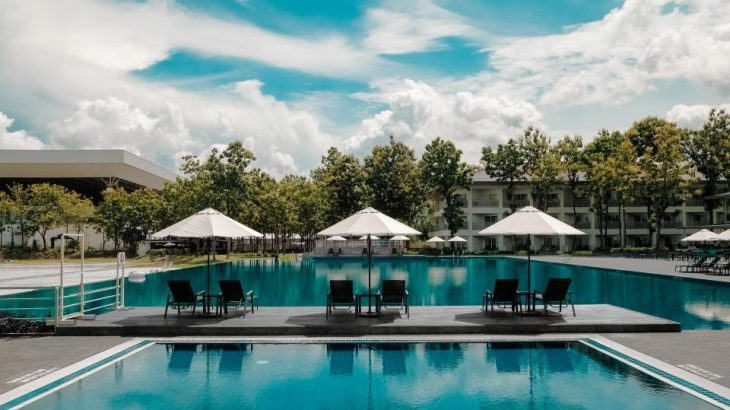 resort-pool-white-umbrellas-trees-background