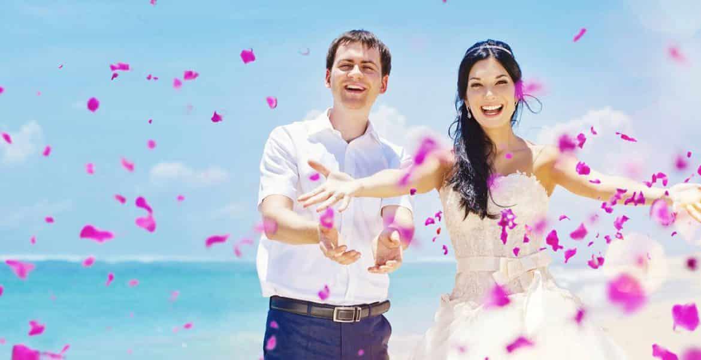 bride-groom-on-beach-throwing-pink-flower-petals