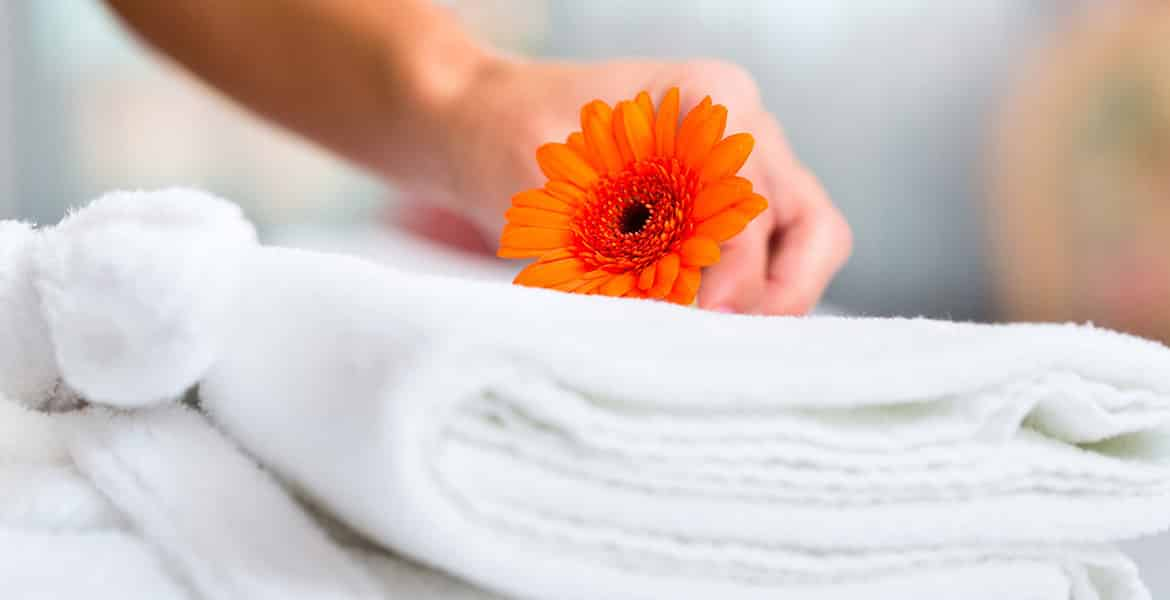 hand-holding-orange-flower-on-white-towel