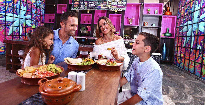 family-eating-at-resort-pink-wall