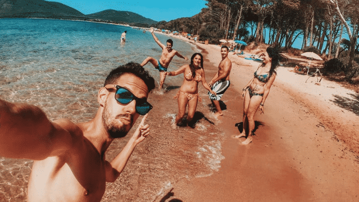 guy-taking-selfie-of-him-and-friends-on-golden-sand-beach
