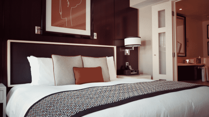hotel-room-bed-with-orange-african-painting-above