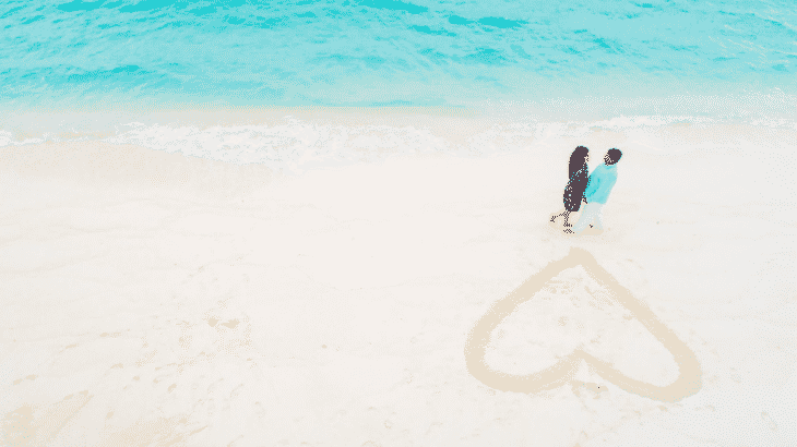 aerial-view-couple-standing-beach-heart-in-sand
