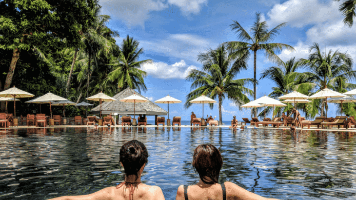 two-women-in-pool-looking-palm-tree-ocean