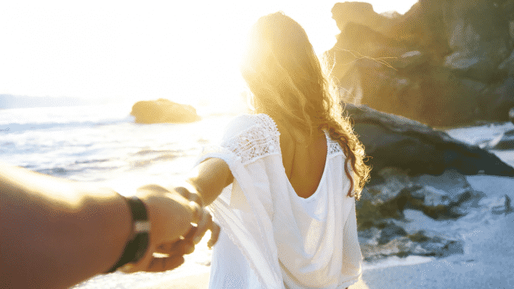 back-of-woman-holding-mans-hand-behind-her-beach
