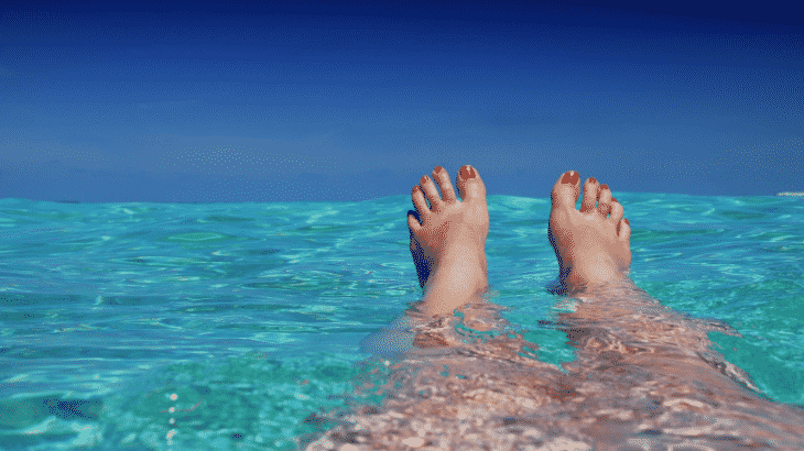 person-floating-clear-blue-water-only-legs-feet-pictured