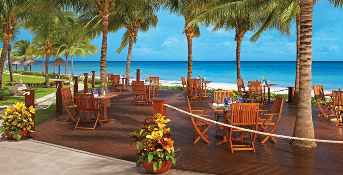 beachfront-dining-wood-tables-blue-ocean-behind