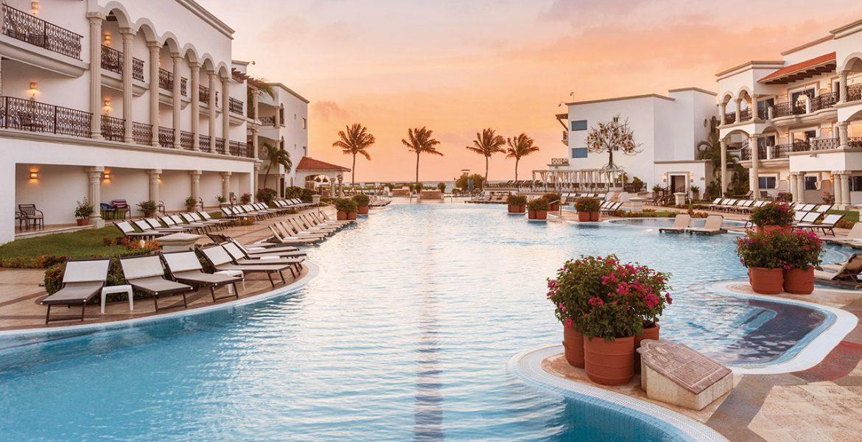 resort-blue-pool-sunset-palm-trees