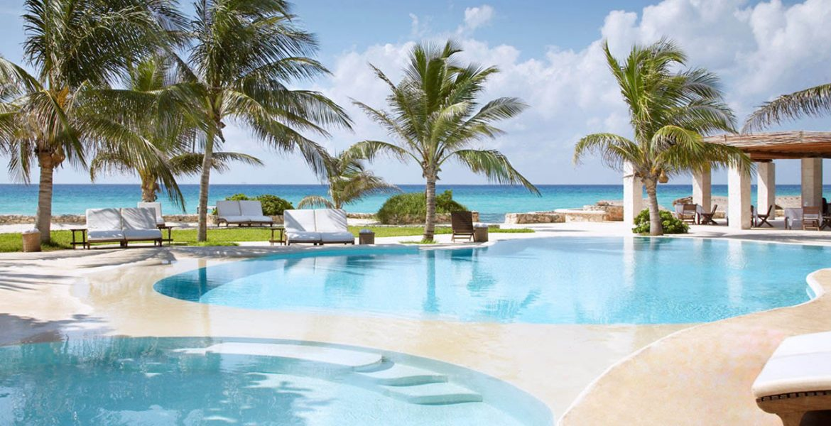 resort-pool-facing-ocean-palm-trees