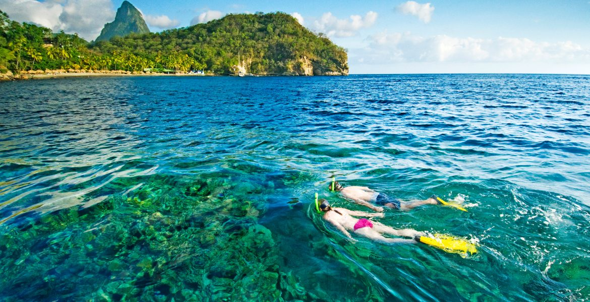 turquoise-water-pitons-peaks-man-woman-snorkeling