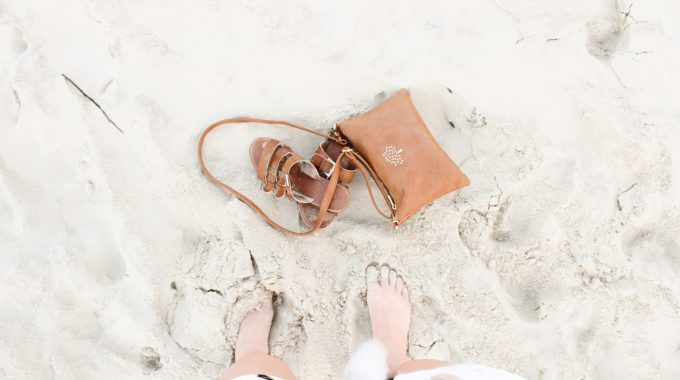 view-womans-feet-in-sand-brown-sandals-purse