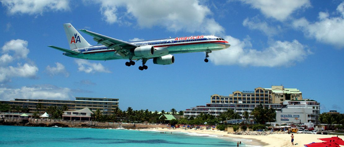 plane-flying-low-over-beach-people-watching