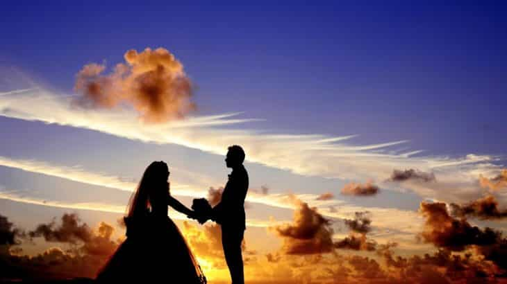 silhouette-bride-groom-in-front-sunset-clouds