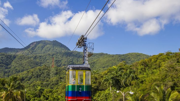colorful-cable-car-hanging-green-lush-mountain-backdrop