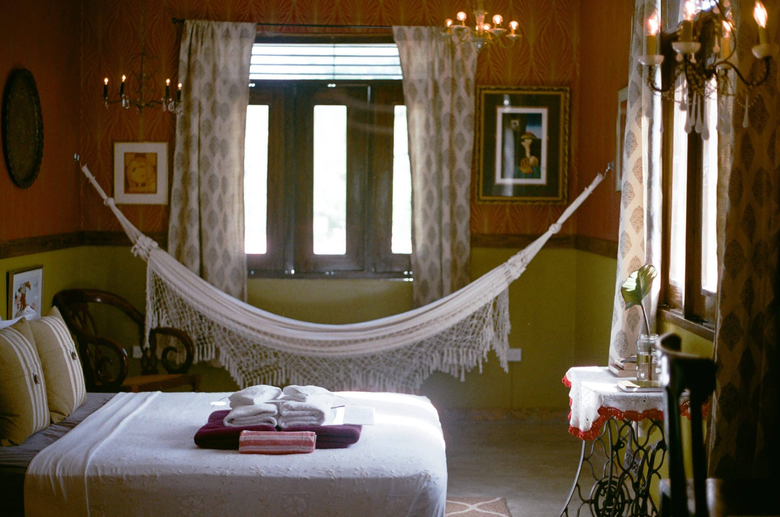 A hammock and cozy bed in a bedroom of the Dreamcatcher hotel