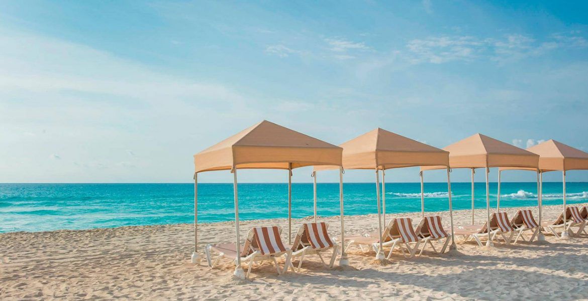 white-sand-beach-lounge-chairs-tan-tents-blue-ocean