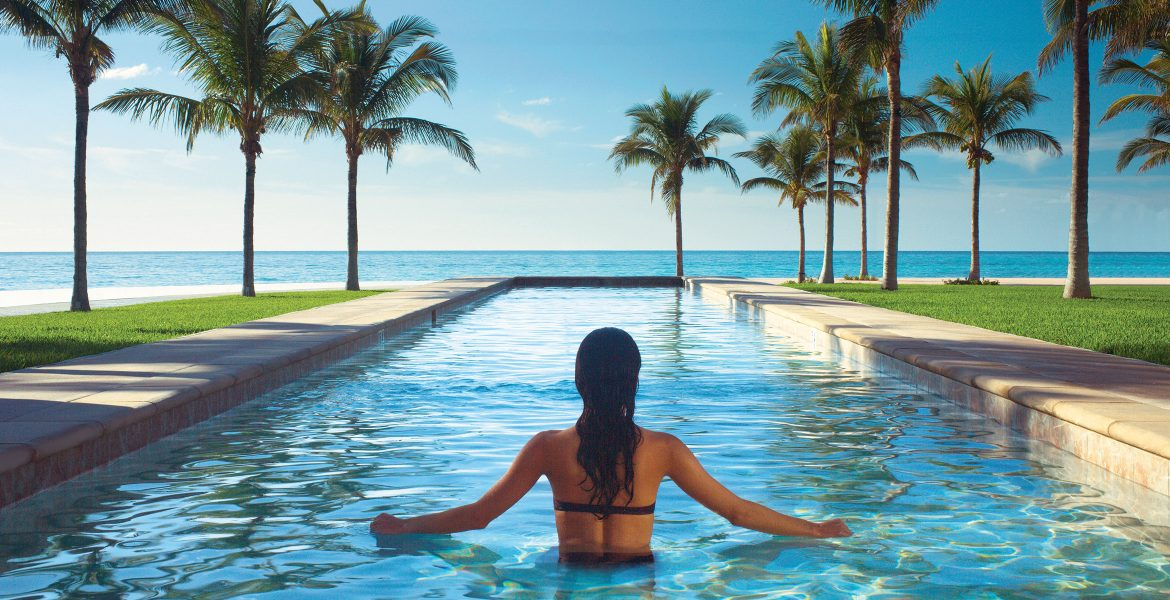 back-of-woman-in-pool-overlooking-ocean-green-palm-trees