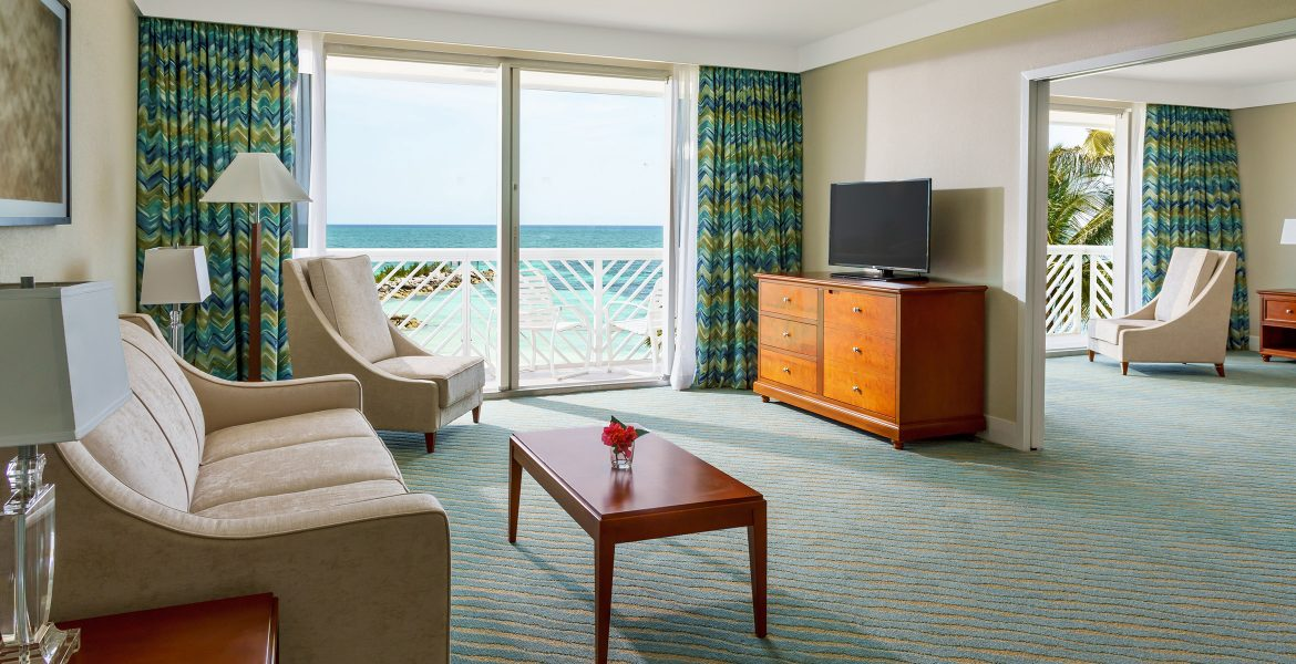 hotel-room-sliding-glass-doors-open-to-balcony-beach-view