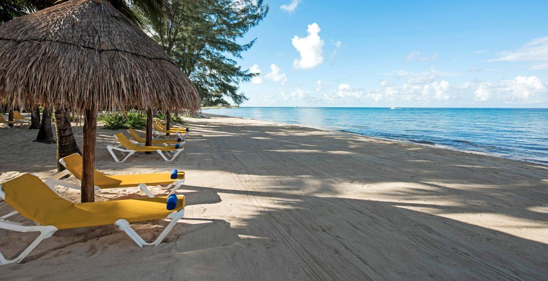 white-sand-beach-blue-ocean-yellow-loungers