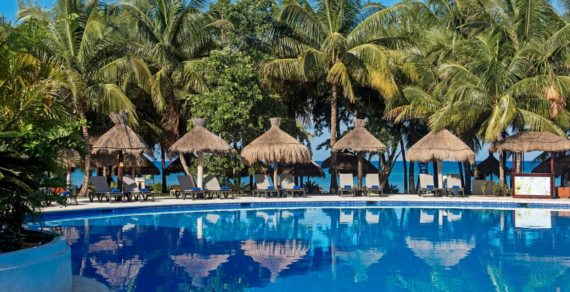 beach-resort-blue-pool-tiki-huts-loungers-green-palm-trees