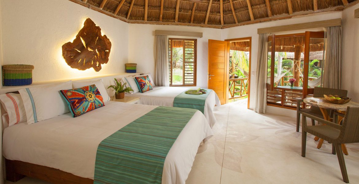 beach-hotel-room-white-beds-green-accents-thatched-roof