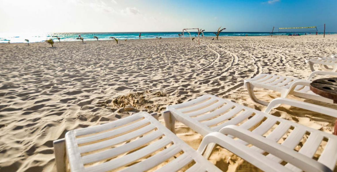 close-up-white-loungers-sand-facing-ocean